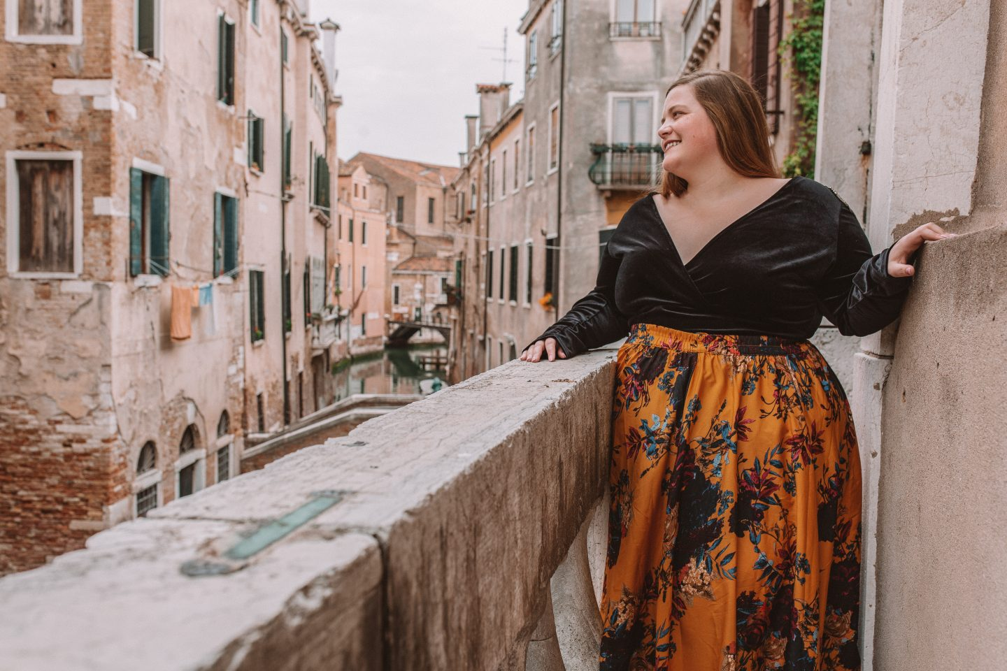 A fashionable plus-sized female posing on a balcony overlooking a canal in Venice, Italy