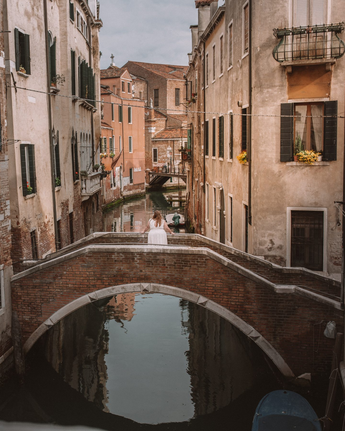 Female standing on bridge over the canal in Venice, Italy