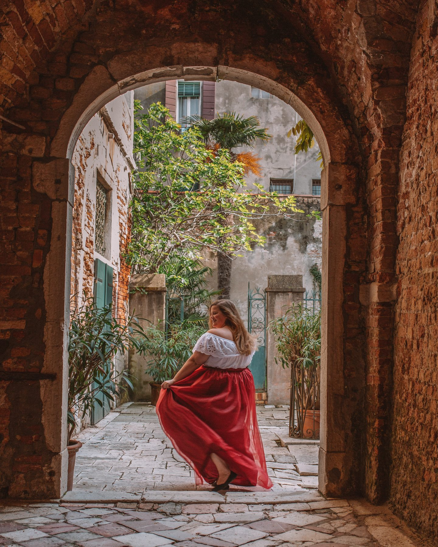 a solo female traveler twirling in a skirt under and italian courtyard arch in Venice, Italy